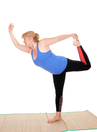 A lovely blond woman is yoga outfit standing on a mat, showing some  poses for yoga exercises, isolated for white background. Stock Photo