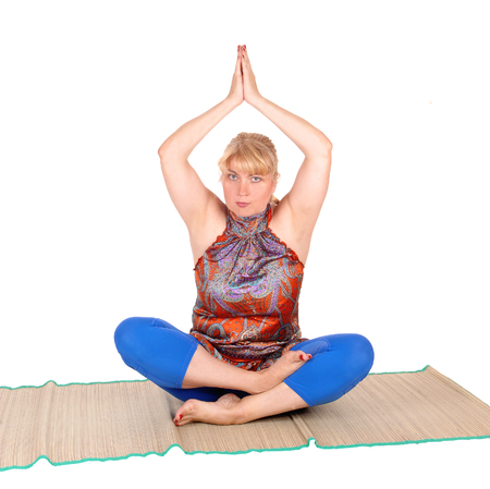 A beautiful blond woman sitting on the floor showing some nice yoga poses, in a blue pants, isolated for white background.