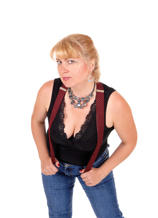 forties: A woman in her forties standing in jeans and a black blouse with red suspenders and a necklace, isolated for white background.