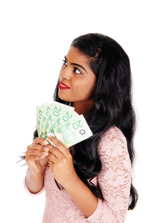 sine: A beautiful young Indian woman holding sine Canadian money, looking up and dreaming, isolated for white background.