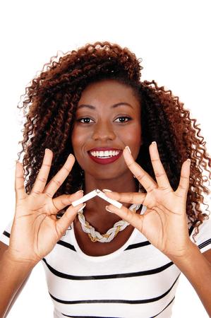 Een gelukkige Afrikaanse Amerikaanse vrouw die een sigaret houdt en het breekt, niet meer rokend, geïsoleerd voor witte achtergrond.