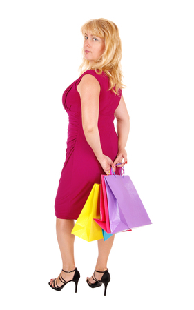forties: A pretty woman in her forties holding the shopping bags, standing in high heels isolated for white background.