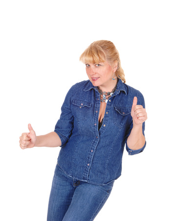 thumps up: A lovely woman in jeans and jeans jacket standing isolated for white  background gesturing with her hands thumps up.