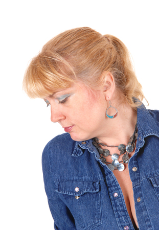 eyes looking down: A portrait image of a pretty blond woman in a jeans jacket, looking down, isolated for white background.