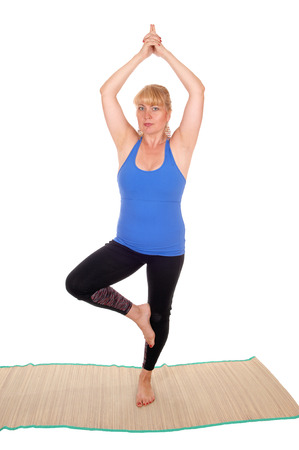 A lovely blond woman is yoga outfit standing on a mat on one leg a  poses for yoga exercises, isolated for white background.
