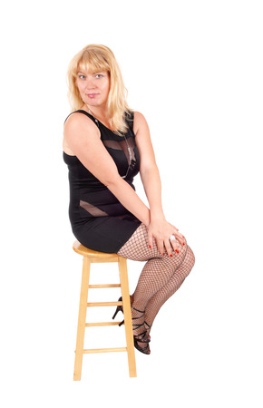 forties: A beautiful woman in her forties sitting in a black evening dress and black stockings on a chair, isolated for white background. Stock Photo