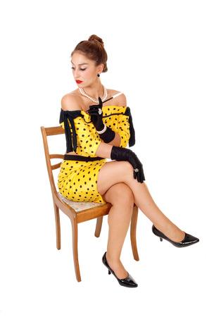Une belle jeune femme dans une robe jaune tenant un long fume-cigarette assis sur une chaise, isolé sur fond blanc.