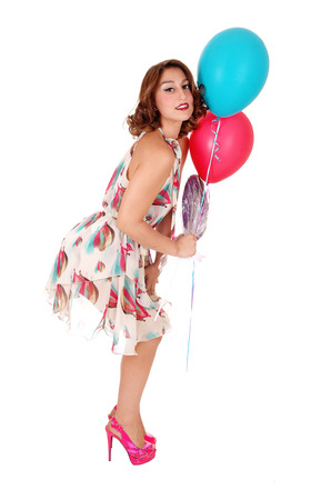 A beautiful woman in a summer dress holding two balloons and standingin profile, isolated for white background.