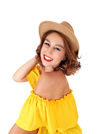 A beautiful young woman standing in a yellow blouse isolated for white background with a cowboy hat on her head.