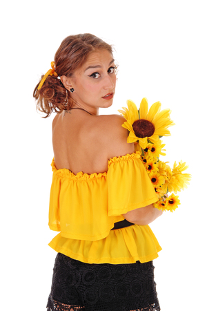 Gorgeous young woman in yellow blouse holding sunflowers, looking over her shoulder, standing isolated for white background.