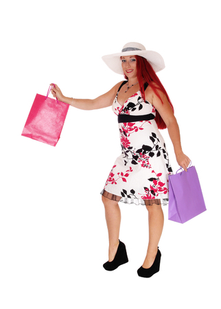 A middle age woman, wearing a white hat and holding some shoppingbags, standing isolated for white background. Stock Photo