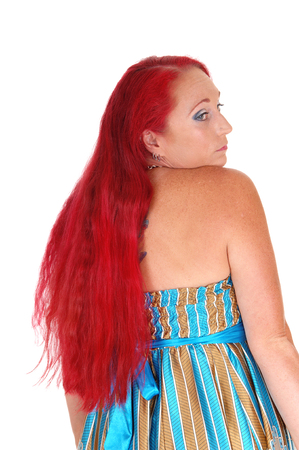 A portrait image of a woman in her thirties, looking over her shoulder,with long red hair, isolated for white background.