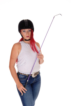 A happy woman with her rider helmet and whip, with long red hairstanding isolated for white background. Stock Photo