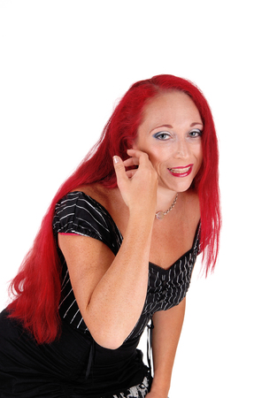 A closeup portrait of a woman with long red hair and a black dress, bending forward, isolated for white background. Stock Photo