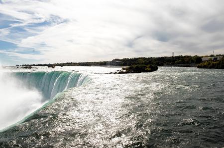 horseshoe falls: The reflecting sun on the Niagara river on the Canadian horseshoe fallsbefore the the edge of the falls.