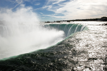 the edge of horseshoe falls: A closeup of the Canadian falls of Niagara Falls  showing the power ofthe water going over the edge wit white mist. Stock Photo