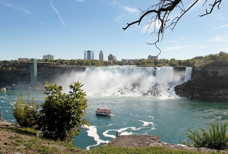 A view of the American falls in Niagara falls with a boat of tourists on theMaid of the Mist, on a sunny day.
