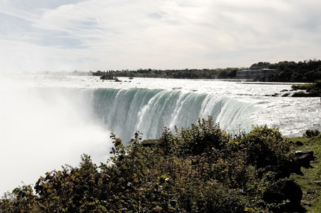 the edge of horseshoe falls: A view of the Niagara falls on the Canadian site with the river flowingover the edge and the mist coming up.
