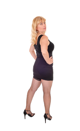forties: A beautiful woman in her forties standing in a black evening dress  from the back, isolated for white background.