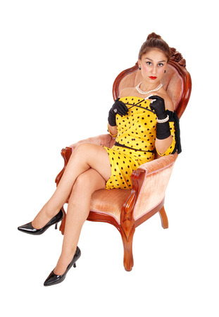 A lovely young woman sitting in a yellow dress in a pink armchair holding a long cigarette holder, isolated for white background. Stock Photo