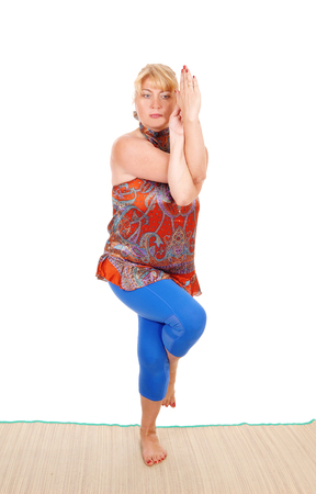 A beautiful blond woman standing on the floor showing some nice yoga poses, in a blue pants, isolated for white background.