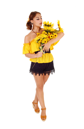 Gorgeous young woman in a yellow blouse holding a bunch of  sunflowers, looking at them, standing isolated for white background.
