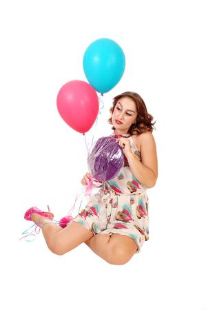 mujer rodillas: Una hermosa mujer joven de rodillas en el suelo que sostiene dos globos y un dulce, aislado de fondo blanco.