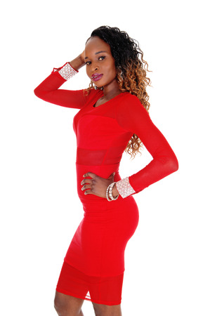 A beautiful young African American woman with a gorgeous figure in a red dress standing in profile isolated for white background. Stock Photo