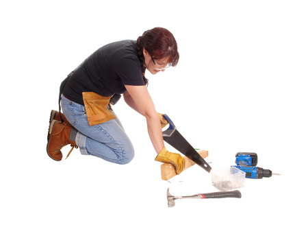 woman kneeling: A middle age woman kneeling on the floor and working with some tools,isolated for white background.