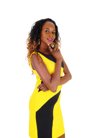A beautiful African American slim woman standing in a black and yellow dress, with one hand on her chin, isolated for white background.