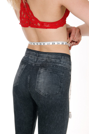A young woman in jeans and a red bra standing from the back measuring her waist, isolated for white background. Stock Photo