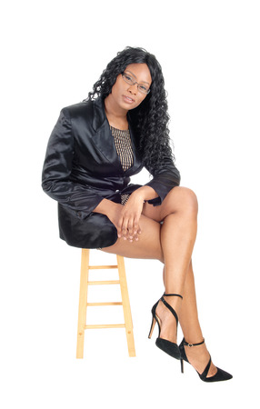 A beautiful African American business woman in a jacket, heels and  glasses sitting isolated for white background. Stock Photo