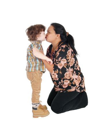 A Filipino nanny kneeling on the floor and kissing the little boy, standing in front of her, isolated for white background.