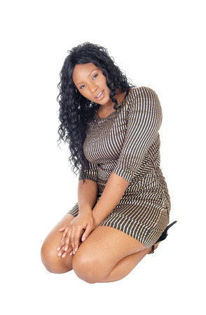 A beautiful African American woman in a short dress and long curlyblack hair kneeling, isolated for white background.