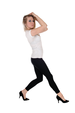 A young slim woman in black tights dancing with her hands on her head, isolated for white background. Stock Photo