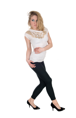 A blond slim young woman standing in black tights and a white blouse and heels, isolated for white background.