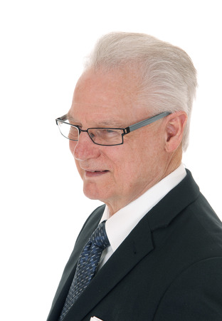 A closeup image of a white hair senior man in a suit and glasses in profile, isolated for white background.