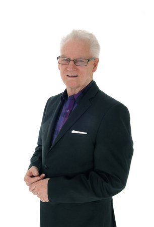 A closeup image of a white hair senior man in a suit and glasses in profile, standing isolated for white background.