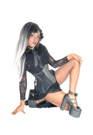 A gorgeous African American woman sitting in a black corset and gray black hair, isolated for white background.