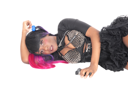A young steam punk African American woman in a short skirt  lying on the floor with red hair, isolated for white background.