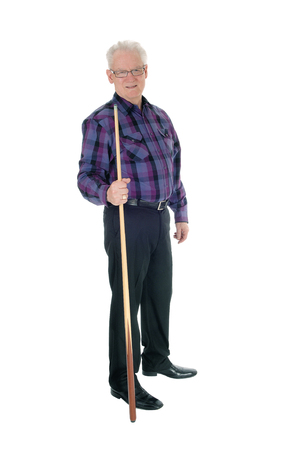 A handsome senior citizen man in a checkered shirt and jeans standing with a billiard cue isolated for white background.