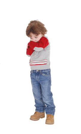 An image of a little three year old boy standing with his arms crossed he is very shy, isolated for white background.