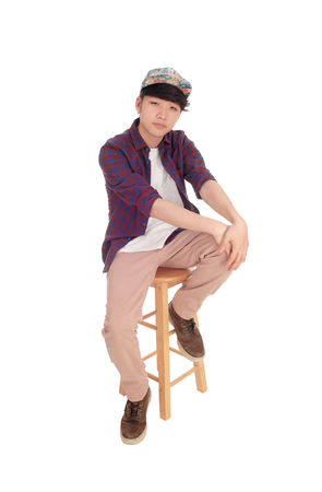 A young Korean teenager sitting on a chair with a cap with his hands on his knee, isolated for white background.