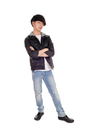 A happy Asian teenager standing in an black jacket crossing his arms, standing, isolated for white background.