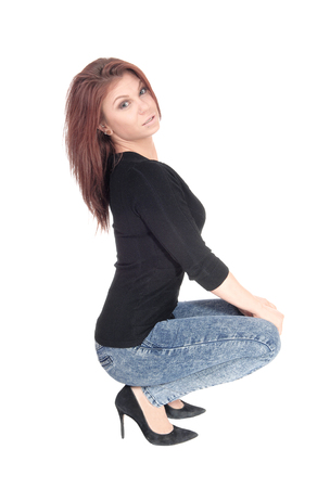 A beautiful young Caucasian woman crouching on the floor, in jeans and black sweater, isolated for white background. Stock Photo