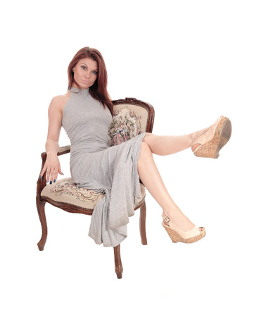 A beautiful young woman in a gray dress sitting in an old armchair, isolated for white background. Stock Photo