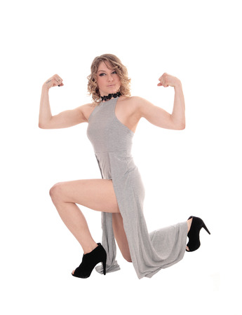 Uma mulher loura bonita que ajoelha-se no assoalho em um vestido cinzento e que dobra seus músculos, isolados para o fundo branco. Foto de archivo - 79722235