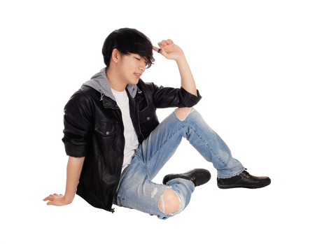 An young Asian teenager sitting in a black leather jacket and ripped jeans on the floor, isolated for white background. Stock Photo