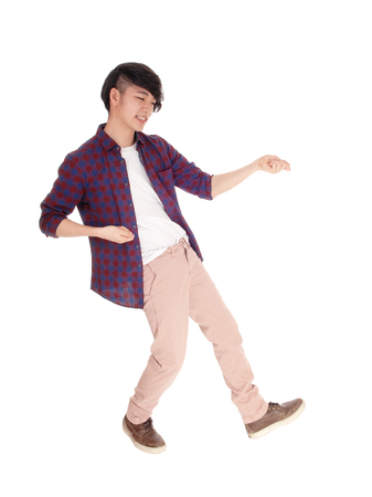 An young Asian man in a checkered shirt and sneakers dancing, isolated for white background.