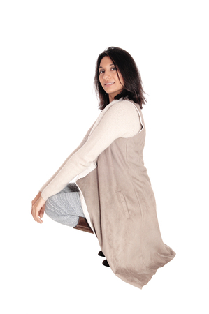 A young Hispanic woman crouching on the floor in a deerskin coat  looking into the camera, isolated for white background.